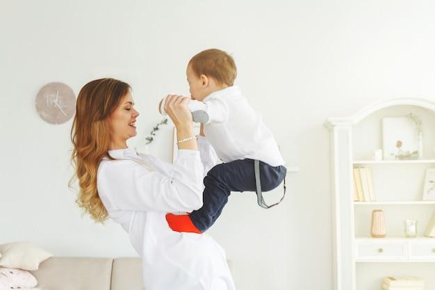 Una giovane madre con un grazioso figlioletto si sta divertendo in un luminoso soggiorno accogliente