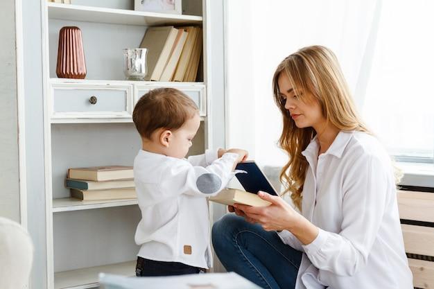 Una giovane madre con un piccolo figlio carino che legge un libro in un luminoso soggiorno accogliente