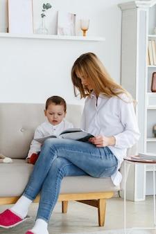 Una giovane madre con un grazioso piccolo figlio che legge una rivista in un luminoso soggiorno accogliente