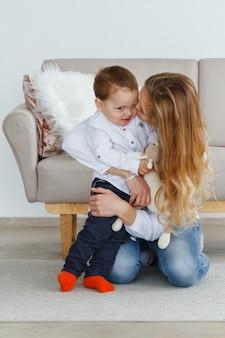 Una giovane madre con un grazioso piccolo figlio seduto sul pavimento in soggiorno