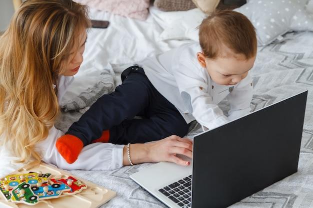 Una giovane madre con il suo amato figlio in camera da letto sul letto con un laptop. lavora a casa con un concetto di bambino