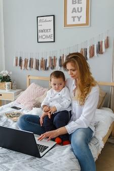 Una giovane madre con il suo amato figlio in camera da letto sul letto con un laptop. lavorare a casa con un concetto di bambino