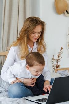 Una giovane madre con il suo amato figlio in camera da letto sul letto con un laptop