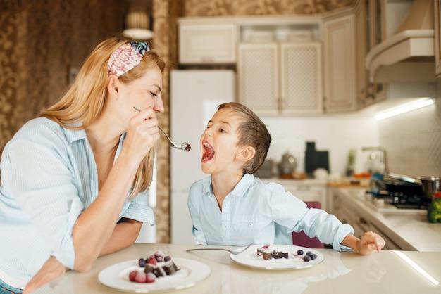 La giovane madre con il suo bambino assaggia la pasticceria al cioccolato.