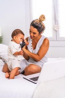 Giovane madre con suo figlio nella stanza in cima al letto, parlando al telefono