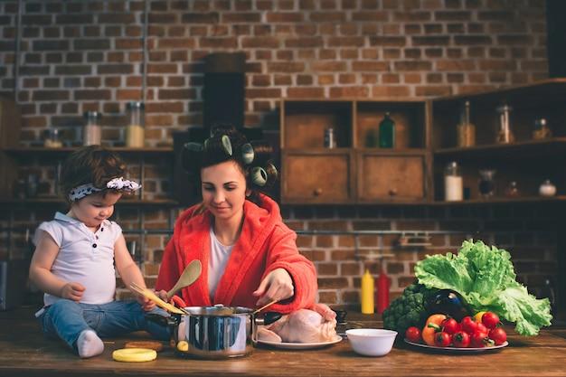 Giovane madre con bambino piccolo nella cucina di casa