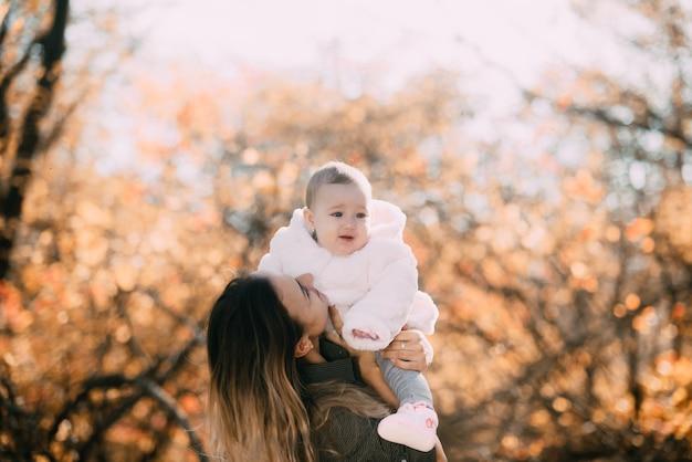 Giovane madre con bambina nella foresta autunnale con un bellissimo
