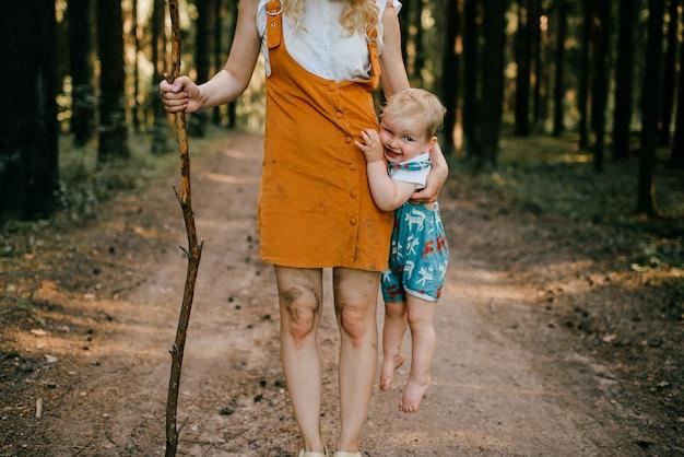 Giovane madre con il bastone che tiene il figlio nella foresta