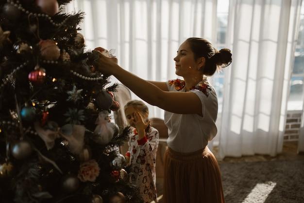 La giovane madre con due piccole figlie in pigiama decora l'albero di capodanno nell'accogliente stanza con una grande finestra luminosa. .