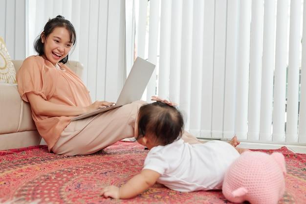 Giovane madre che lavora al computer portatile