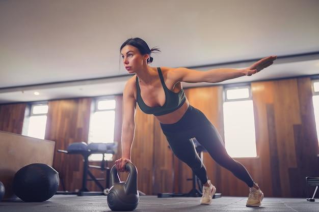 Giovane ragazza motivata facendo esercizio di plancia utilizzando kettlebell con una mano in palestra, foto a figura intera, copia dello spazio