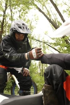 Giovane motociclista in casco e guanti che tiene stretta la mano dell'amico mentre lo sollevava da terra