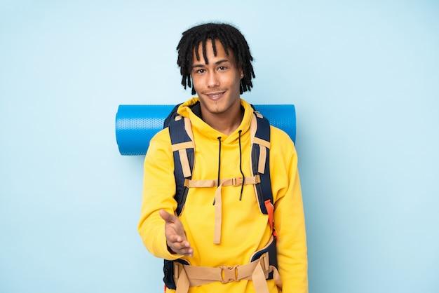Uomo afroamericano del giovane alpinista con un grande zaino isolato su una stretta di mano blu dopo il buon affare