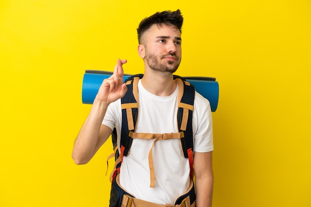 Giovane alpinista caucasico con un grande zaino isolato su sfondo giallo con le dita incrociate e augurando il meglio