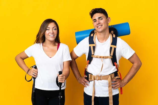Coppia giovane alpinista con un grande zaino su giallo in posa con le braccia al fianco e sorridente