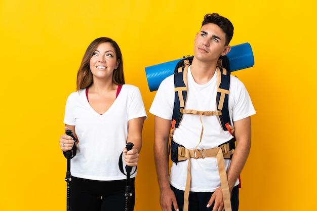 Coppia giovane alpinista con un grande zaino su giallo pensando un'idea mentre guarda in alto