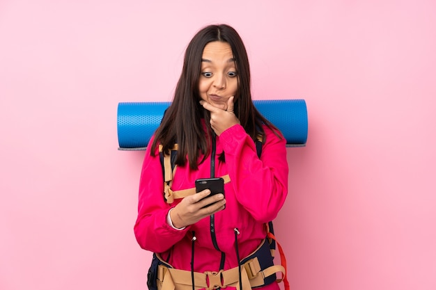 Ragazza giovane alpinista con un grande zaino sopra il pensiero rosa isolato e l'invio di un messaggio