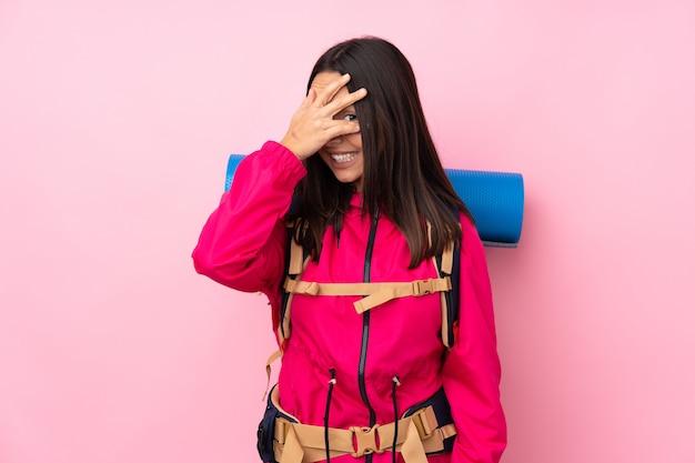 La ragazza giovane dell'alpinista con un grande zaino sopra il rivestimento rosa isolato della parete osserva a mano e sorridendo