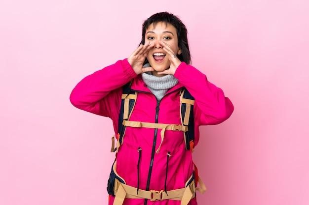 Ragazza giovane alpinista con un grande zaino sopra la parete rosa che grida con la bocca spalancata
