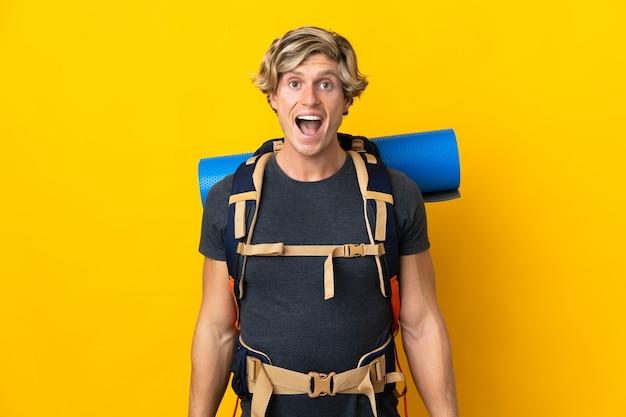 Uomo giovane alpinista isolato con espressione facciale sorpresa