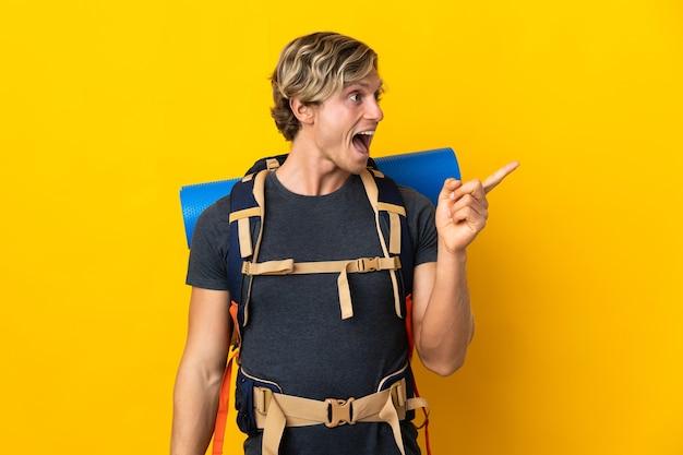 Il giovane alpinista sopra il giallo isolato che intende realizzare la soluzione mentre solleva un dito
