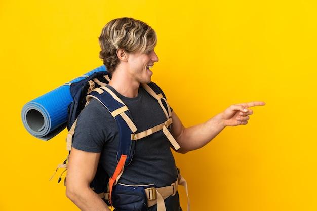 Uomo giovane alpinista sopra il dito puntato giallo isolato al lato e che presenta un prodotto