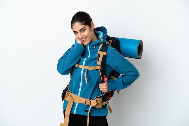 Giovane alpinista con un grande zaino su sfondo isolato ridendo