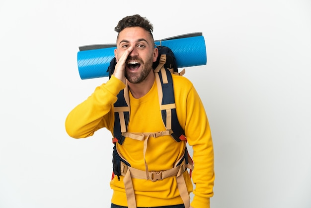 Giovane alpinista uomo con un grande zaino su sfondo isolato gridando con la bocca spalancata