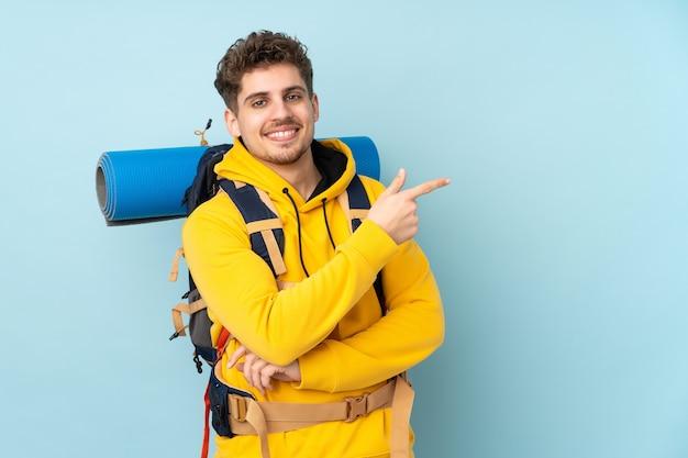 Uomo giovane alpinista con un grande zaino isolato sul dito puntato blu a lato