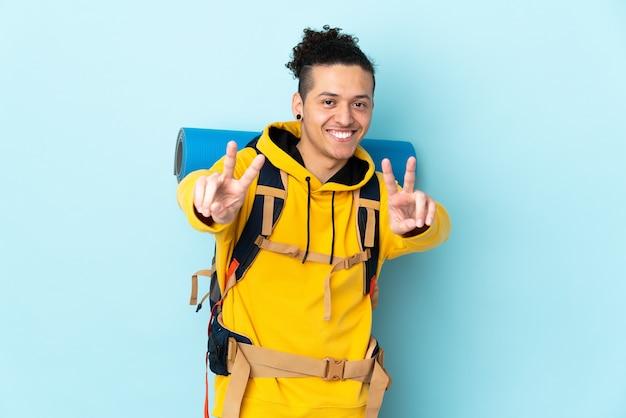 Uomo giovane alpinista con un grande zaino sopra la parete blu isolata che sorride e che mostra il segno di vittoria