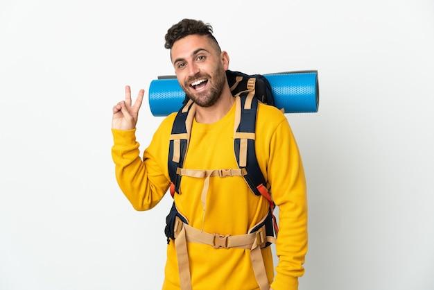 Uomo giovane alpinista con un grande zaino sopra la parete isolata che sorride e che mostra il segno di vittoria