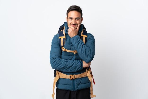 Uomo giovane alpinista con un grande zaino isolato sul muro bianco ridendo