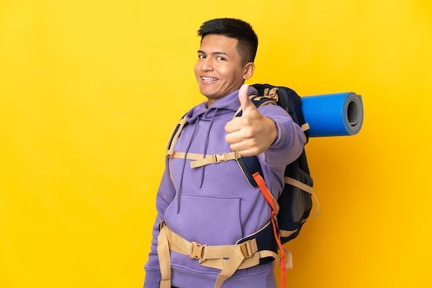 Giovane alpinista con un grande zaino isolato su sfondo giallo con il pollice in alto perché è successo qualcosa di buono