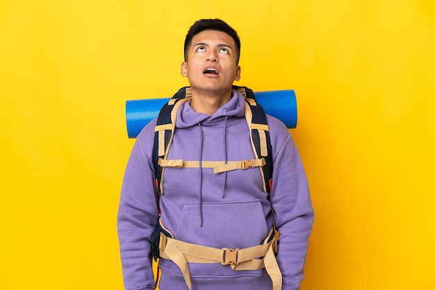 Uomo giovane alpinista con un grande zaino isolato