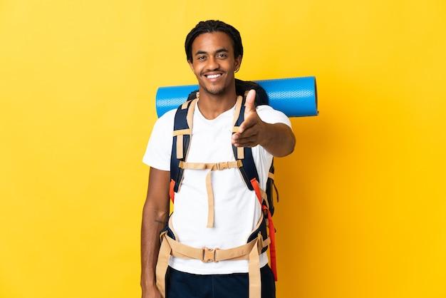Giovane alpinista con trecce con un grande zaino isolato su sfondo giallo si stringono la mano per chiudere un buon affare