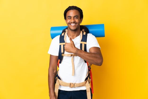 Giovane alpinista con trecce con un grande zaino isolato sulla parete gialla che dà un pollice in alto gesto