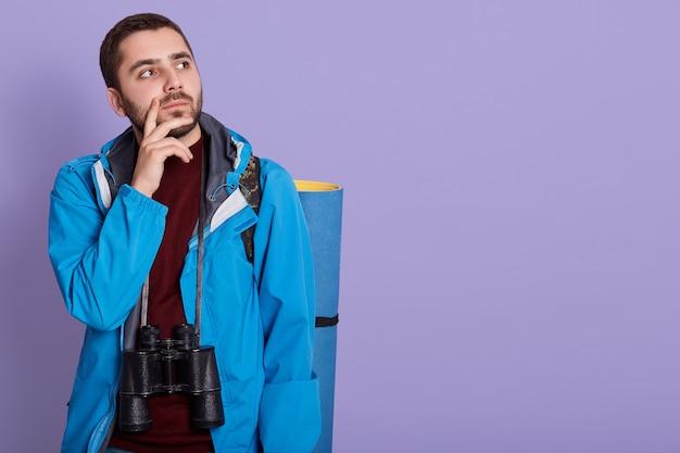 Uomo giovane alpinista con tappetino e binocolo isolato su sfondo lilla pensando a qualcosa