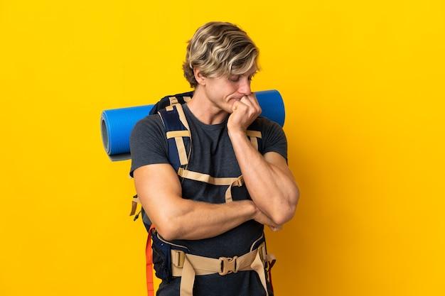 Uomo giovane alpinista sopra giallo che ha dubbi
