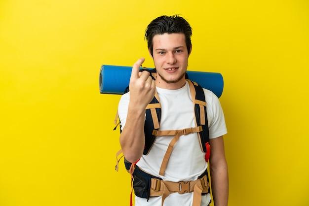 Giovane alpinista russo con un grande zaino isolato su sfondo giallo che fa un gesto imminente