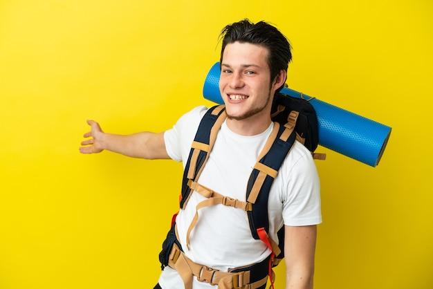 Giovane alpinista russo con un grande zaino isolato su sfondo giallo che allunga le mani di lato per invitare a venire