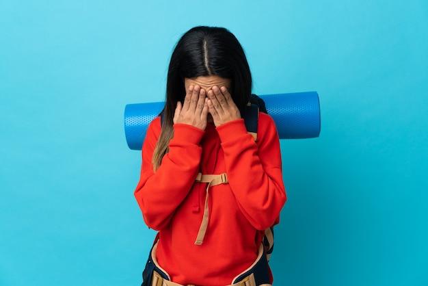 Donna giovane alpinista con zaino con espressione stanca e malata