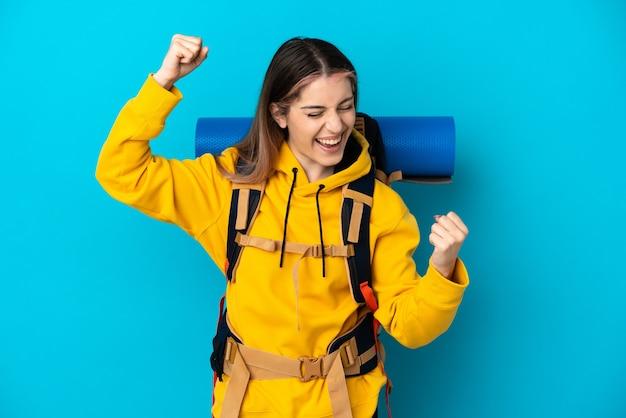 Donna giovane alpinista con un grande zaino isolato sulla parete blu che celebra una vittoria