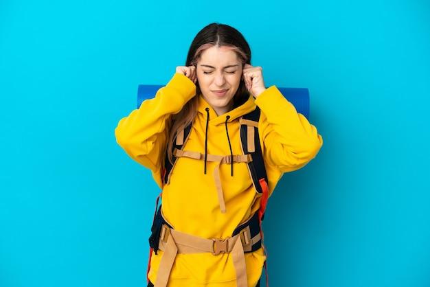 Giovane donna alpinista con un grande zaino isolato sulla parete blu frustrata e che copre le orecchie