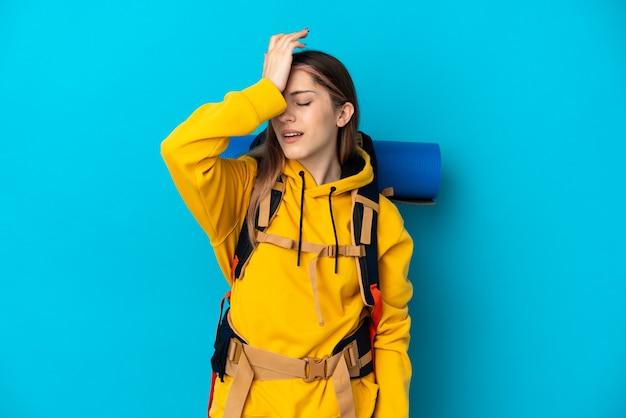 La giovane donna alpinista con un grande zaino isolato sulla parete blu ha realizzato qualcosa e intende la soluzione