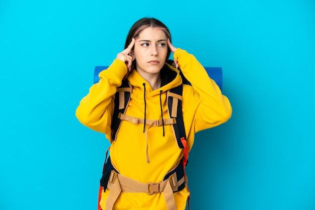 Donna giovane alpinista con un grande zaino isolato sulla parete blu avendo dubbi e pensando