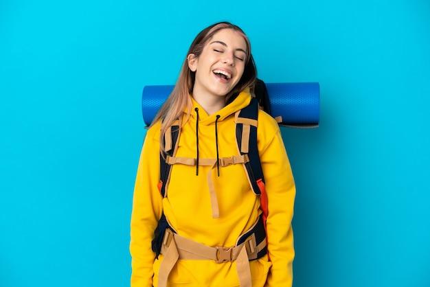 Donna giovane alpinista con un grande zaino isolato sul muro blu ridendo
