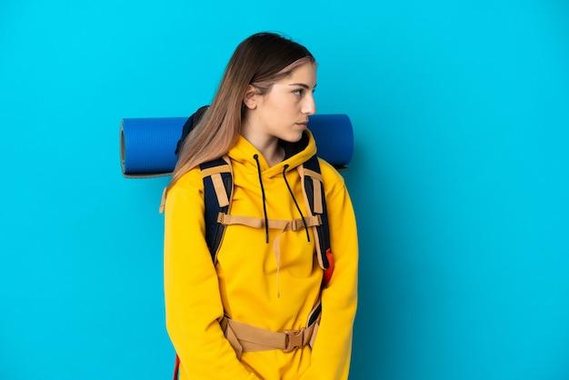 Donna giovane alpinista con un grande zaino isolato sulla parete blu che guarda al lato
