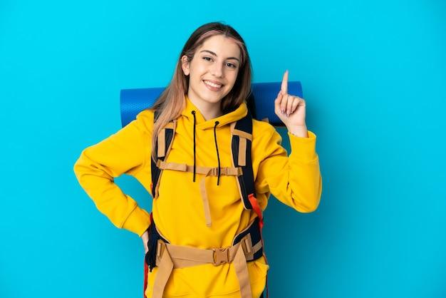 Giovane donna alpinista con un grande zaino isolato sulla parete blu che mostra e alzando un dito in segno del meglio