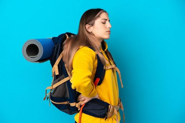 Giovane donna alpinista con un grande zaino isolato sulla parete blu che soffre di mal di schiena per aver fatto uno sforzo