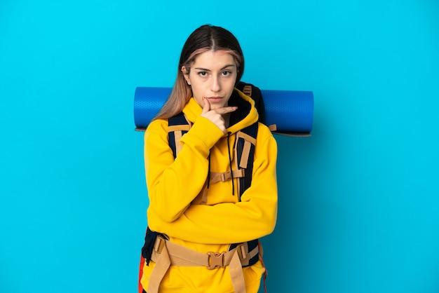Donna giovane alpinista con un grande zaino isolato sul pensiero muro blu